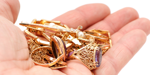 hand of  aman holding loose gold jewelry including rings bracelets and chains